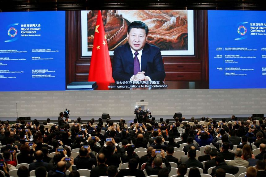 Attendees listen to a speech by China's President Xi Jinping shown on a screen during the opening ceremony of the third annual World Internet Conference in Jiaxing, Zhejiang province on Nov 16, 2016.