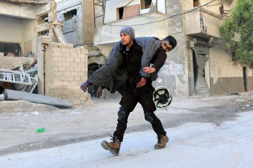 A Syrian civil defence volunteer carries an injured man on Nov 19, 2016, following a reported air strike on Aleppo.