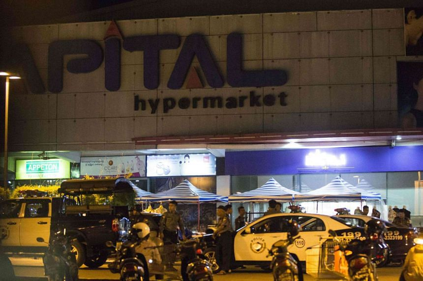 Myanmar police personnel stand guard at a supermarket where three bombs exploded in Yangon on Nov 20, 2016.