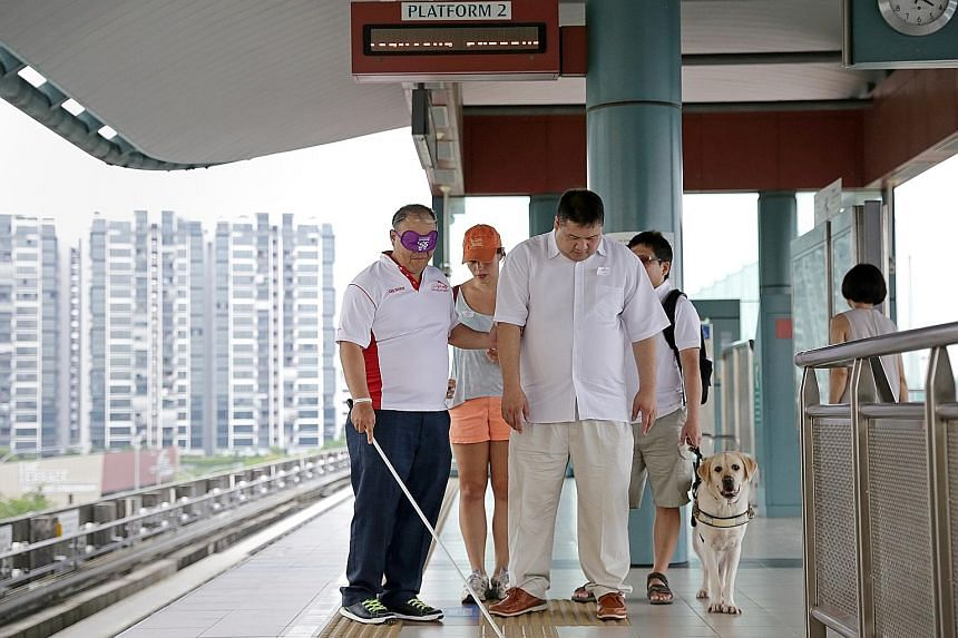 Mr Luke Cheong, 49, one of the exercise participants, trying to locate the path to the lift using a cane, together with Mr Bernard Goh, 45. Guide dog mobility instructor Zara Linehan, 35, is giving them periodic reminders to help them along. With the