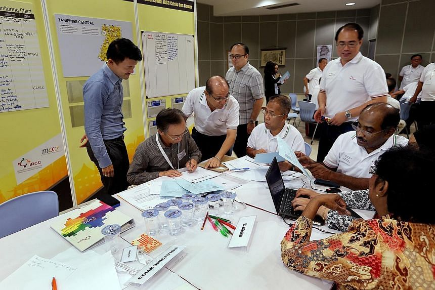 Mr Baey Yam Keng (far left), Parliamentary Secretary, Ministry of Culture, Community and Youth, observing a discussion between religious and community leaders during a crisis preparedness exercise in March this year.