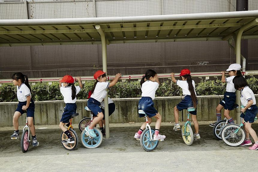 Children at Kyuden Elementary School riding unicycles during recess. It is part of a culture that urges elementary school children to do things on their own, including taking the subway or walking around city neighbourhoods