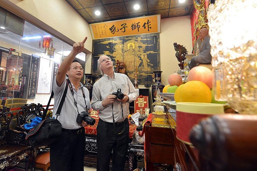 Professor Dean (left) and Dr Hue (far left), seen here at Leong San See Temple in Race Course Road, have been recording, photographing, analysing and translating Chinese inscriptions into English from 63 Buddhist and Taoist temples, clans and guild h