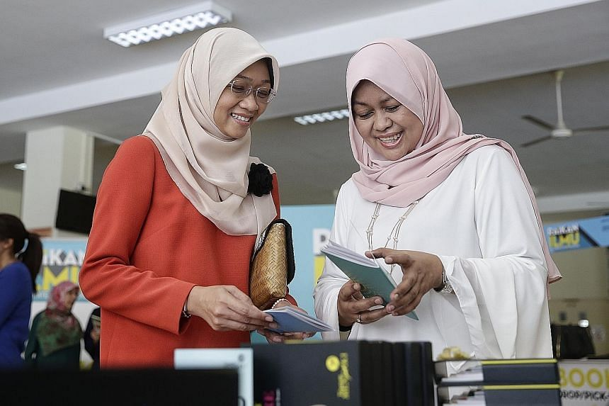 Ms Rahayu (left) and Ms Tuminah at the launch of the guidebook, My Early Adventure, at Bedok Green Primary School yesterday.