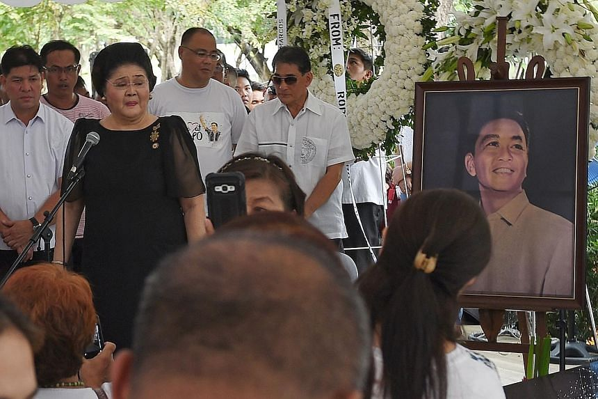 Former first lady Imelda Marcos (in black) speaking to supporters at the grave of her husband, the late dictator Ferdinand Marcos, at the national heroes' cemetery in Manila yesterday, a day after the controversial burial took place.