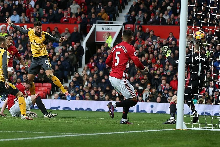 Arsenal substitute Olivier Giroud (No. 12) heading in his side's equaliser off a cross from Alex-Oxlade Chamberlain, another player who came off the Gunners' bench, to earn his side an unlikely draw with Manchester United. United boss Jose Mourinho (