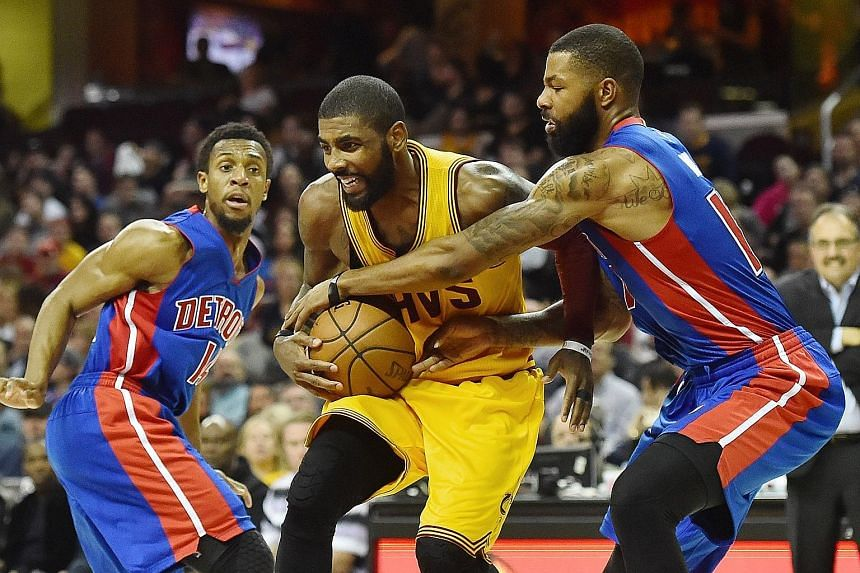 Detroit's Marcus Morris (far right) trying to strip Cleveland's Kyrie Irving of the ball as Ish Smith watches at Quicken Loans Arena. Irving led the hosts with 25 points as they won the National Basketball Association game 104-81.