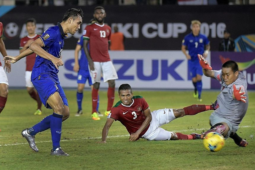 Thailand striker Teerasil Dangda (left) tapping in his third goal and Thailand's fourth to seal his side's 4-2 win over Indonesia. The AFF Cup defending champions next face Singapore.