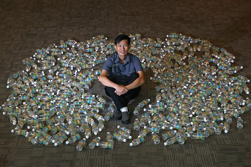 Environmentalist Tan Hang Chong surrounded by 432 bottles of Newater, which is equivalent to 151 litres of water - the average water consumption of each person each day in Singapore last year.