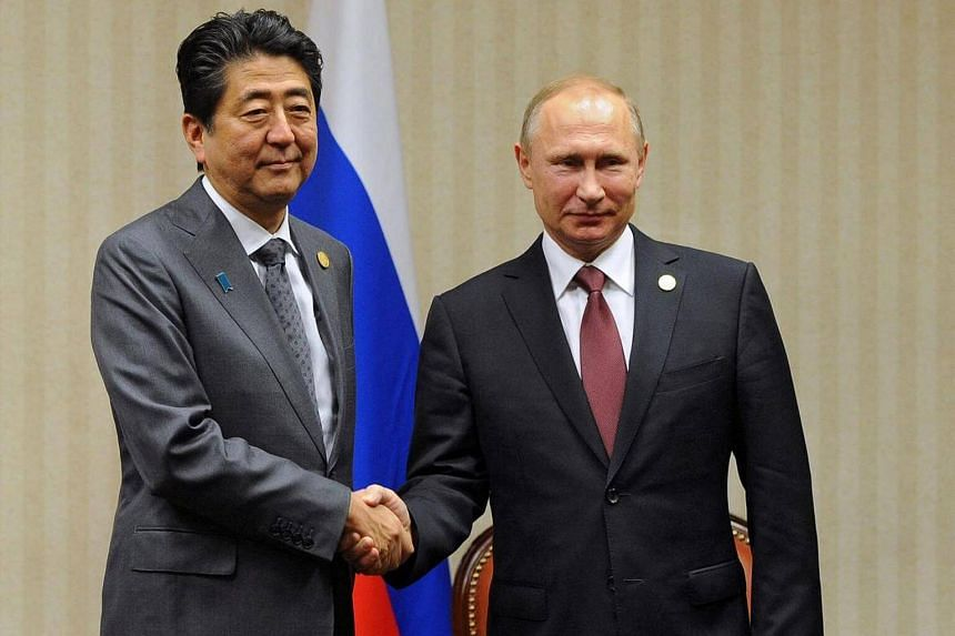 Russian President Vladimir Putin and Japanese Prime Minister Shinzo Abe shake hands during their meeting in Lima, Peru on Nov 19, 2016.
