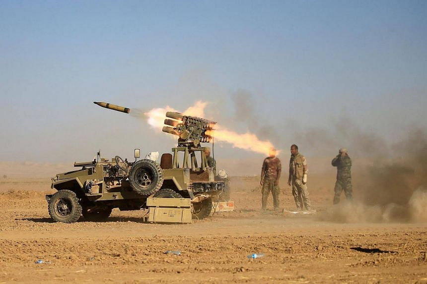 Shi'ite fighters fire a rocket towards Islamic State militants during a battle with ISIS soldiers at the airport of Tal Afar west of Mosul, Iraq on Nov 18, 2016.