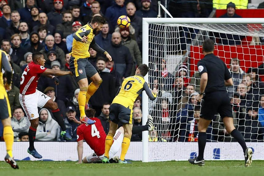 Arsenal striker Olivier Giroud leaps high to head in a late equaliser against Manchester United at Old Trafford.