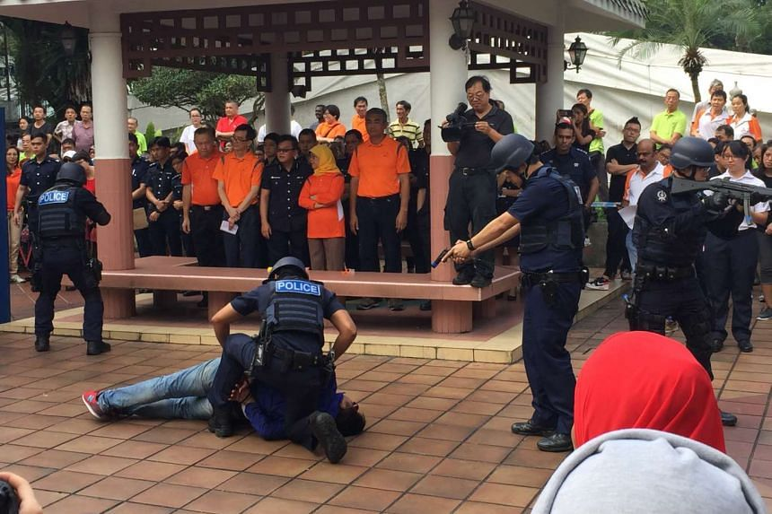 Residents take part in an emergency drill simulating an armed terrorist attack on a cafe, as part of Marsiling ward's Community Emergency Preparedness Day on Sunday (Nov 20).