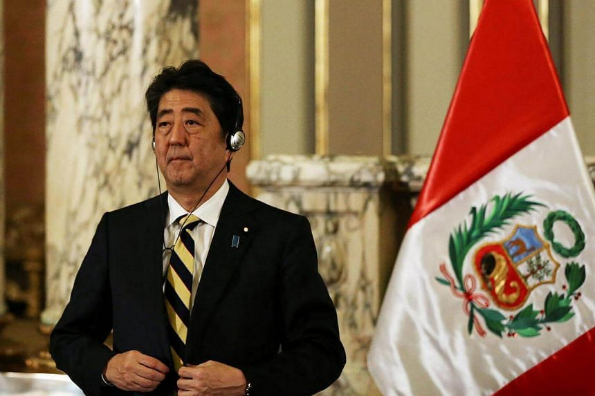 Japanese Prime Minister Shinzo Abe buttons his jacket after a meeting at the presidential palace ahead of the 2016 Apec (Asia-Pacific Economic Cooperation) summit in Lima, Peru on Nov 18, 2016.