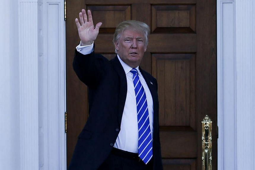 US President-elect Donald Trump waves as former governor Mitt Romney leaves after a meeting at the clubhouse of Trump National Golf Club in New Jersey.