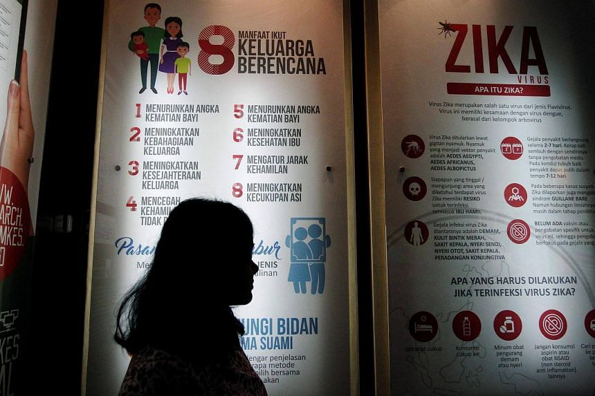 A woman stands near a poster explaining about the Zika virus at the Ministry of Health office in Jakarta, Indonesia on Sept 2, 2016.