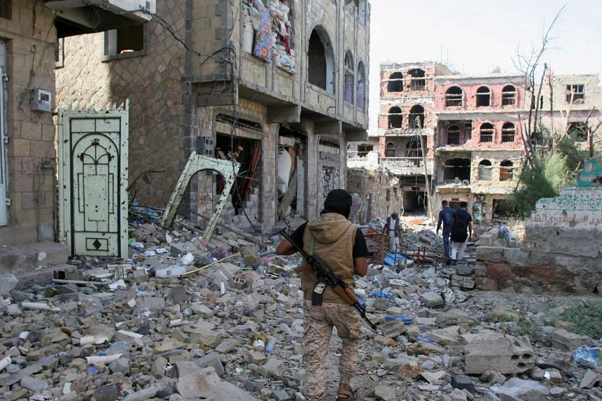 A pro-government fighter walks at the site of recent battles between Houthi fighters and pro-government fighters, on the second day of a 48-hour ceasefire in the southwestern city of Taiz, Yemen, on Nov 20, 2016.