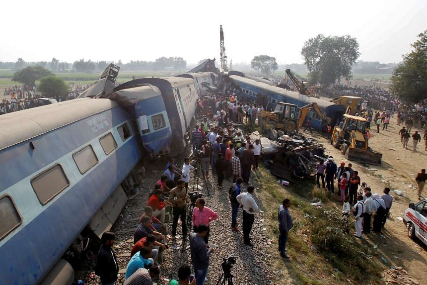 Rescue workers search for survivors at the site of a train derailment in Pukhrayan, south of Kanpur city, India, on Nov 20, 2016.