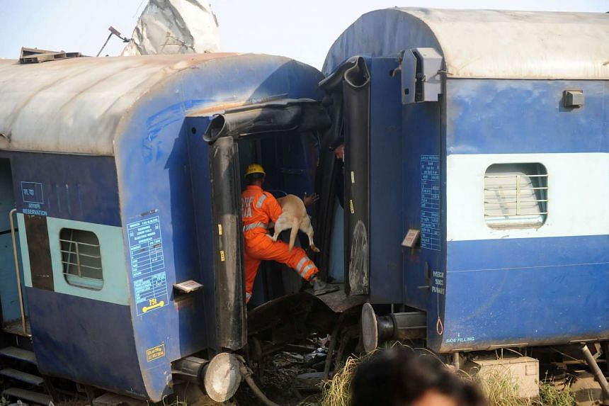Indian rescue workers search for survivors in the wreckage of a train that derailed near Pukhrayan in Kanpur district on Nov 20, 2016.