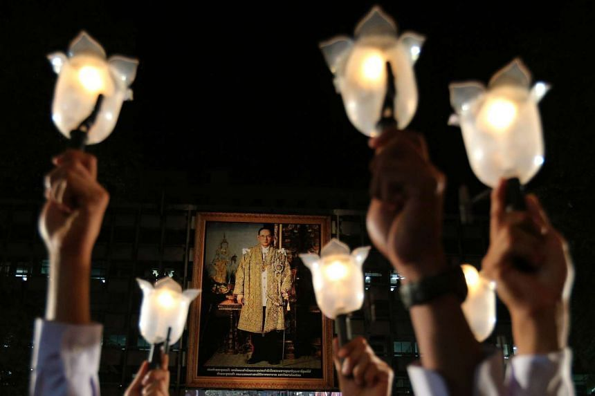 Thai mourners hold up candles in front of a large portrait of the late Thai King Bhumibol Adulyadej on a building at Siriraj Hospital in Bangkok on Nov 13, 2016.