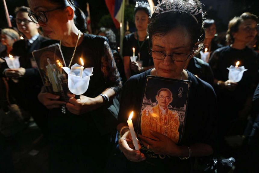 Thai mourners hold pictures of the late Thai King Bhumibol Adulyadej as they light candles at Siriraj Hospital in Bangkok on Nov 13, 2016.