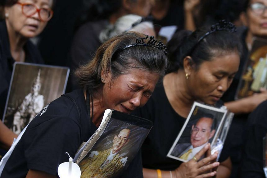 A Thai mourner holding a portrait of late Thai King Bhumibol Adulyadej cries while waiting for the start of a candlelight ceremony in honour of the monarch at Siriraj Hospital in Bangkok on  Nov 13, 2016.