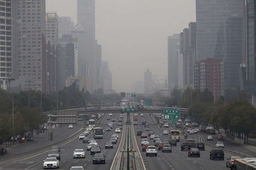 Smog hovers over a main road in Beijing on Nov 17, 2016. From Feb 15, highly polluting old cars will be banned from being driven whenever air quality alerts are issued in the city or neighbouring regions.