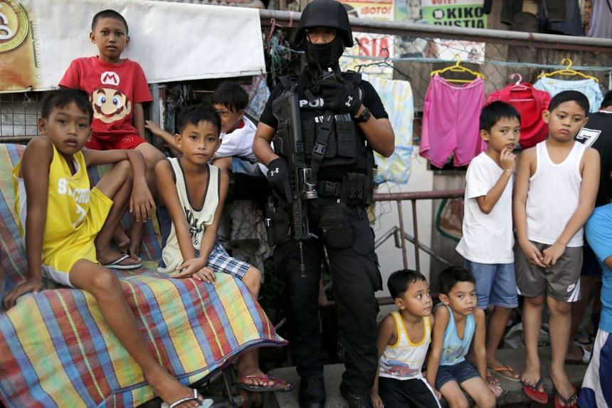 A member of the Special Weapons and Tactics team standing guard as children look on during an anti-drug operation at an informal settlers community in Pasig city, east of Manila, on Nov 9, 2016.