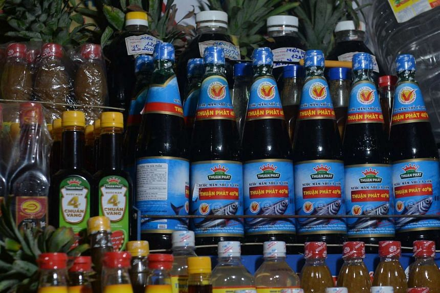 Bottles of fish sauce (in blue) are displayed for sale at a stand inside a local market in downtown Hanoi on Nov 21, 2016.