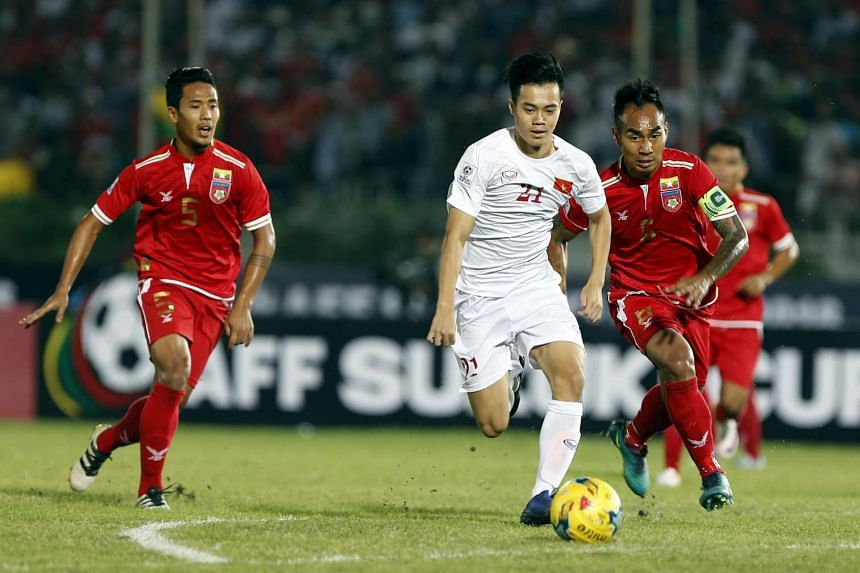 Nguyen Van Toan (centre) of Vietnam in action against Yan Aung Kyaw (right) of Myanmar during the AFF Suzuki Cup Group B soccer match in Thuwanna Football stadium in Yangon, on Nov 20, 2016.