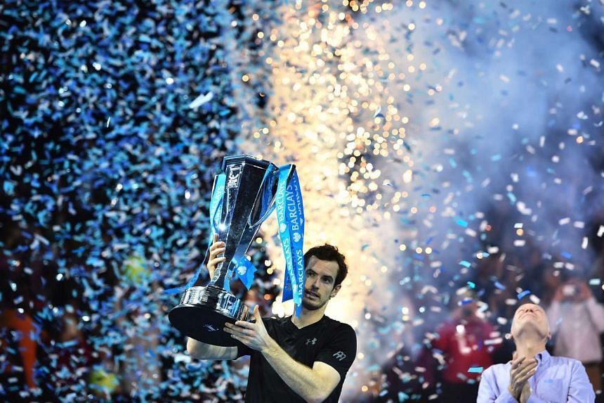 Britain's Andy Murray celebrate with the trophy after winning the men's singles final against Serbia's Novak Djokovic on the eighth and final day of the ATP World Tour Finals tennis tournament in London on Nov 20, 2016.