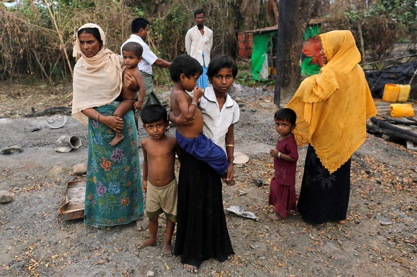 A family stands beside remains of a market which was set on fire, in Rohingya village outside Maungdaw, in Rakhine state on Oct 27, 2016.