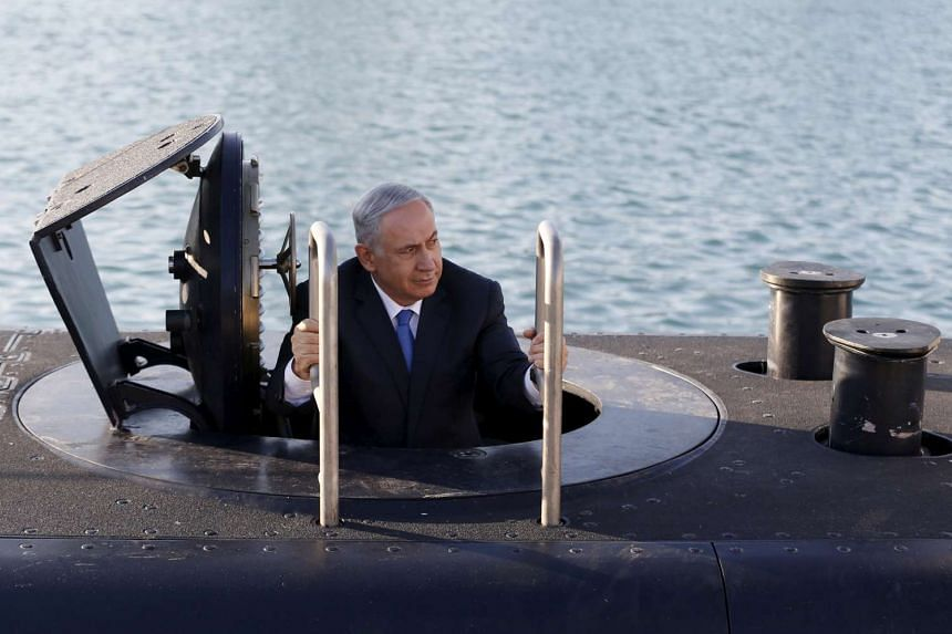 Israeli Prime Minister Benjamin Netanyahu climbs out after a visit inside the Rahav, the fifth submarine in the fleet, after it arrived in the Haifa port on Jan 12, 2016.