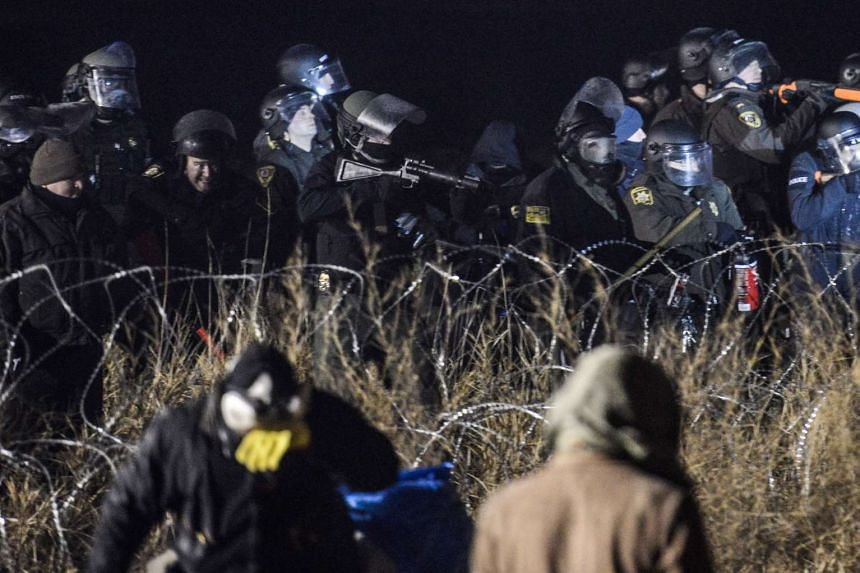 Police confront protesters with a rubber bullet gun during a protest against plans to pass the Dakota Access pipeline near the Standing Rock Indian Reservation in North Dakota on Nov 20, 2016.
