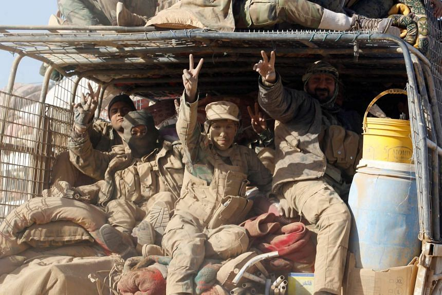 Members of the Shi'ite Badr Organisation fighters ride in a military vehicle during a battle with Islamic State in Iraq and Syria militants at the airport of Tal Afar west of Mosul, Iraq, on Nov 20, 2016.