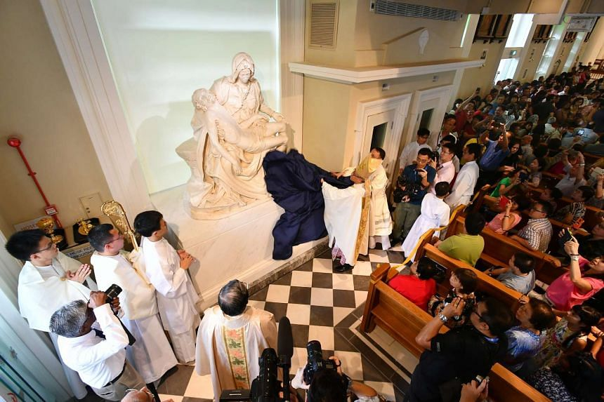 Archbishop William Goh Seng Chye unveiling the replica of Michelangelo's famous 1499 Pieta sculpture at the first mass at the newly restored Cathedral of Good Shepherd on Nov 20, 2016.