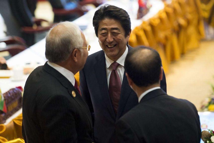 Malaysia's Prime Minister Najib Razak (left) talks with Japanese Prime Minister Shinzo Abe (center) during the ASEAN-Japan Summit in Vientiane on Sept 7, 2016.