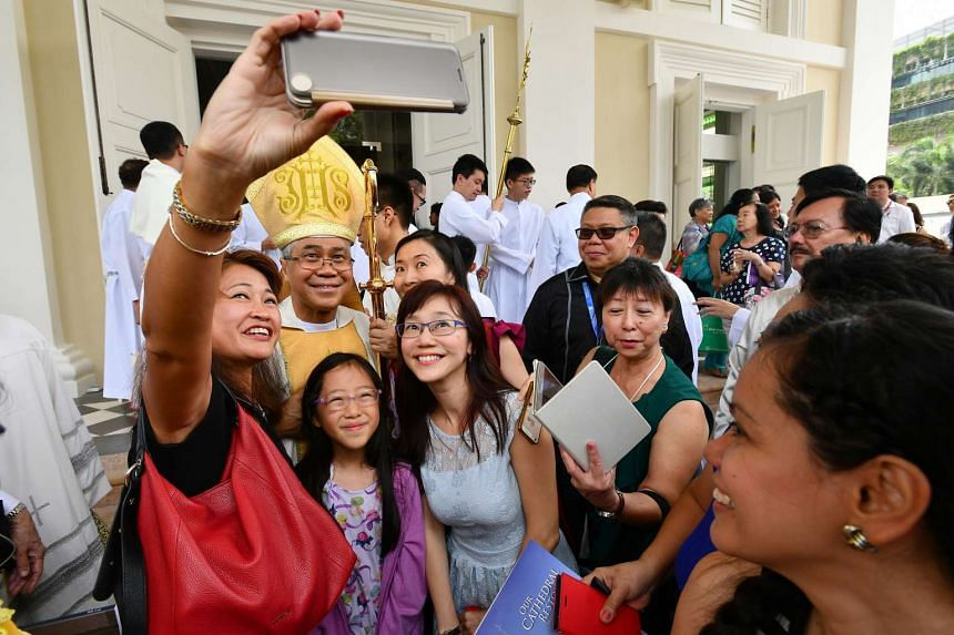 Archbishop William Goh Seng Chye taking photographs with worshippers after the mass at Cathedral of Good Shepherd on Nov 20, 2016.