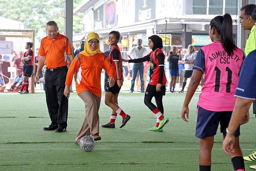 Madam Halimah kicking off a futsal match yesterday at Woodlands Recreation Centre, flanked by Mr Lim Hock Chee, the vice-chairman of the Marsiling Citizens' Consultative Committee.