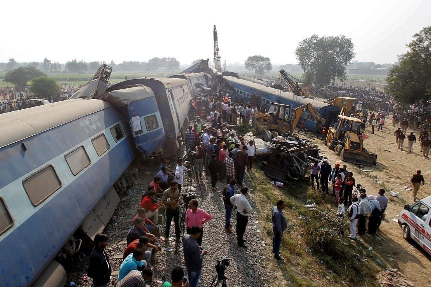 A crowd gathers as rescue workers search for survivors at the site of a train derailment in Pukhrayan, south of Kanpur city, in the north Indian state of Uttar Pradesh. Survivors said the packed train suddenly rolled off the tracks early yesterday wh