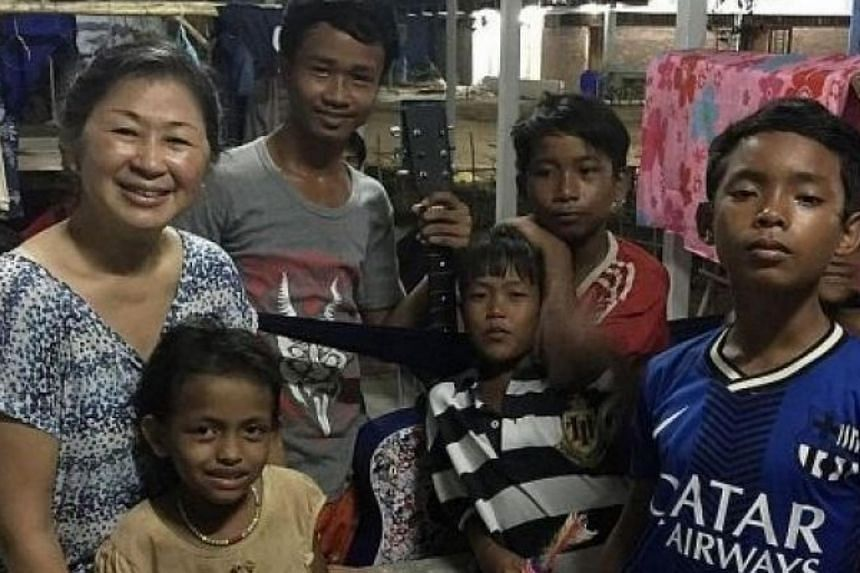 Former music teacher Aileen Ong with some of the children living in Cambodia's Smile Village, which Madam Ong helped build.