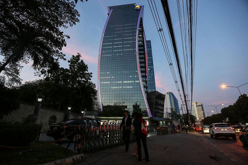 The Stock Exchange of Thailand building stands illuminated at dusk in Bangkok, Thailand.