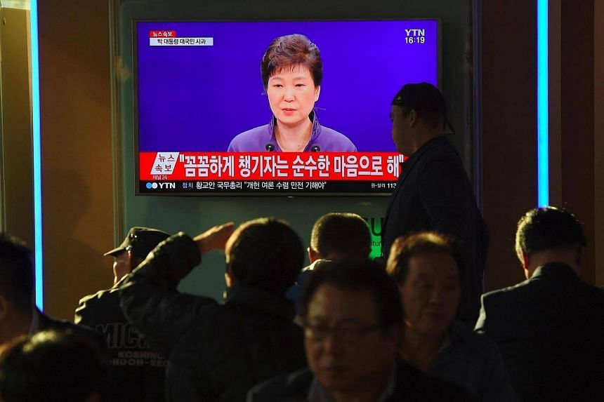 People watch a television news report showing South Korean President Park Geun Hye making a public apology, at a railway station in Seoul on Oct 25, 2016.