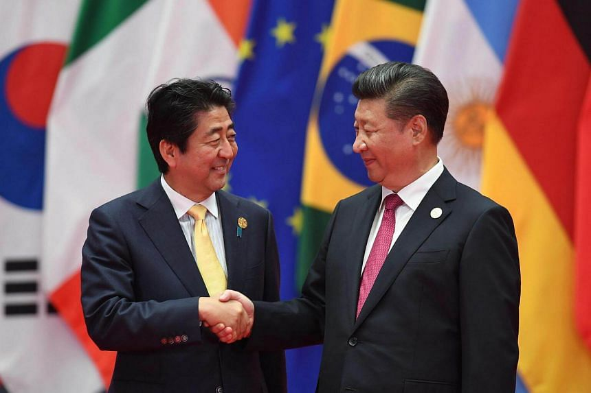 Japanese Prime Minister Shinzo Abe (left) shakes hands with Chinese President Xi Jinping at the G20 leaders' retreat in Hangzhou on Sept 4, 2016.