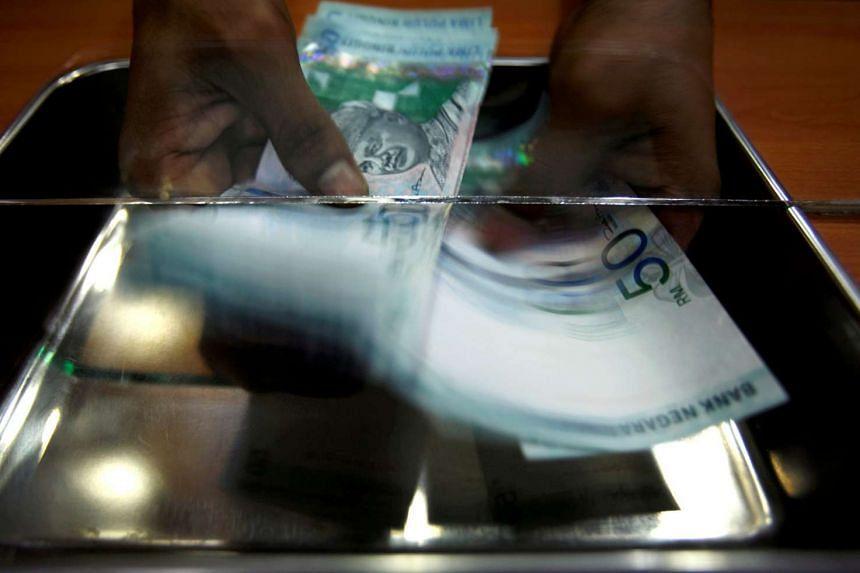 A money changer counts ringgit at a shop in Putrajaya, outside Kuala Lumpur, on Oct 26, 2007.