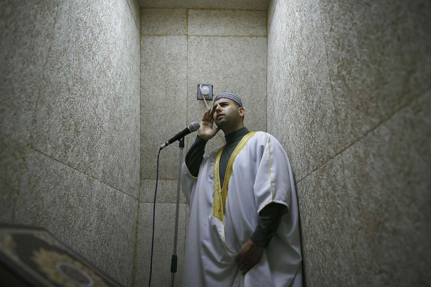 Firas Kazaz, a Palestinian muezzin -- the person appointed to recite the Muslim call to prayer -- calls for prayer from the Al-Aqsa mosque compound in Jerusalem's Old City, on Nov 21, 2016.