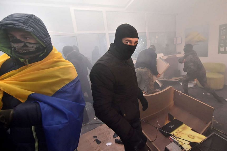 Activists of some far-right Ukrainian parties loot a branch of Russian Sberbank in the centre of Kiev on Nov 21, 2016 after a rally marking the third anniversary of the Euromaidan protests.