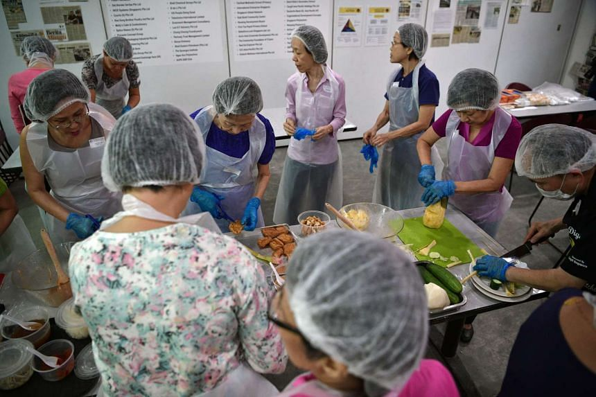 "Participants, including retired primary school May Foong (left) who is in her 60s, learn how to make siew mai and rojak during the ""Cook, Bake and Serve"" workshop held by Dignity Kitchen on Nov 22, 2016."