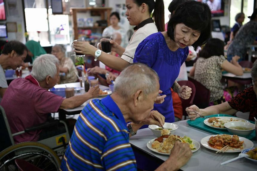 Retired primary school teacher May Foong (right), in her 60s, attending to elderly visitors from the Apex Day Rehab Centre tucking in to the siew mai and rojak made by participants during a workshop held by Dignity Kitchen on Nov 22, 2016.