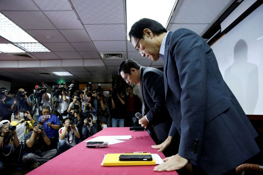 TransAsia Airways chairman Vincent Lin (center) bows his head during a news conference after its board had approved a move to wind down the company and that all flights would be suspended in Taipei on Nov 22, 2016.